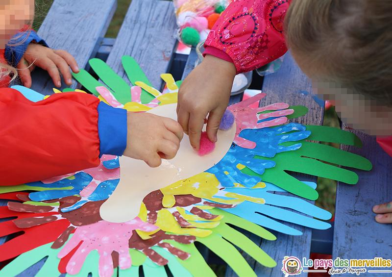 paon en empreintes de mains multicolores