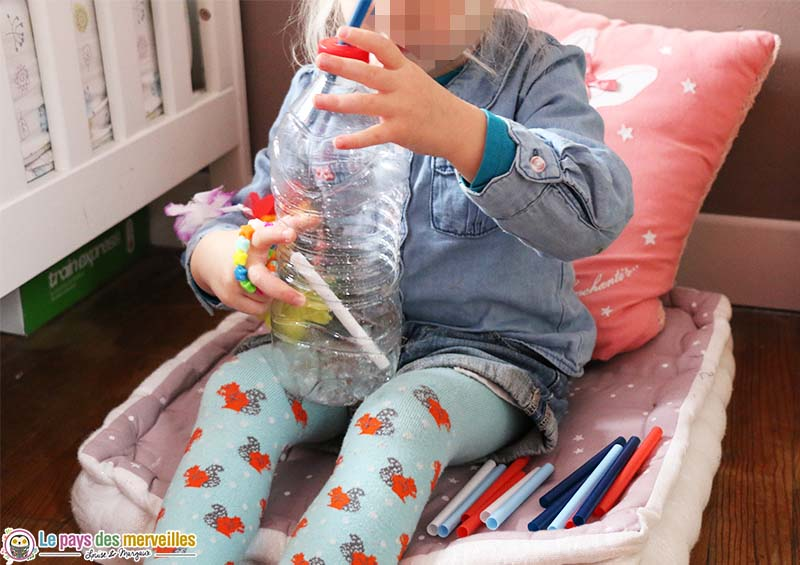 activité de motricité fine avec des pailles et une bouteille