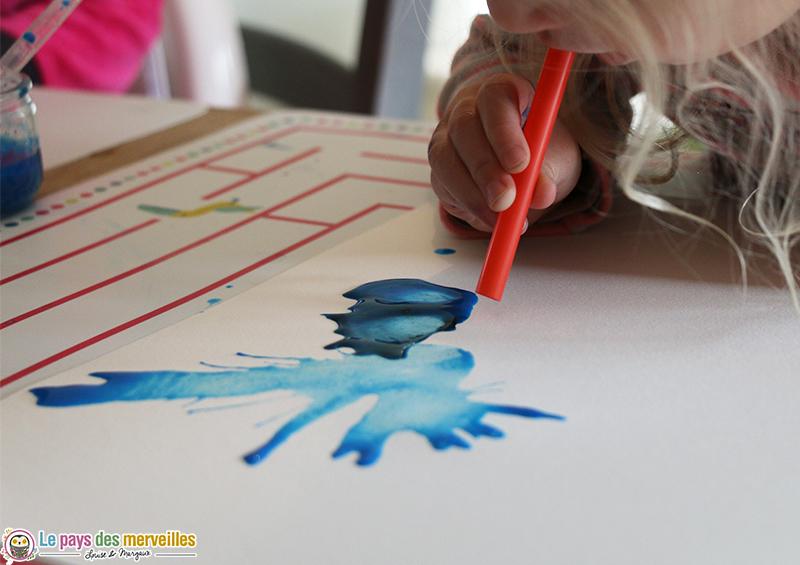 Souffler sur de la peinture avec une paille coupée en deux