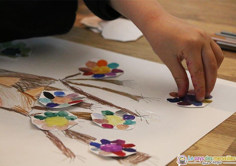 Coller des fleurs peintes sur un dessin d'arbre