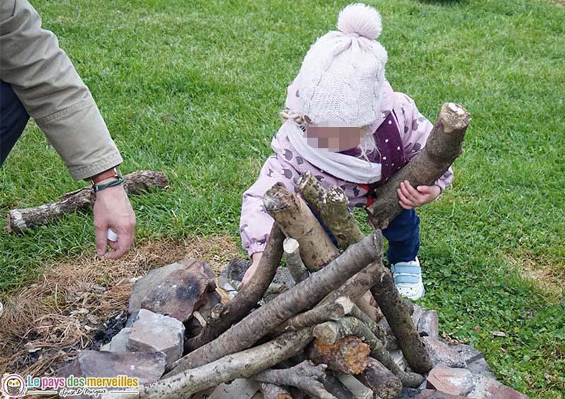enfant qui prépare un feu de bois