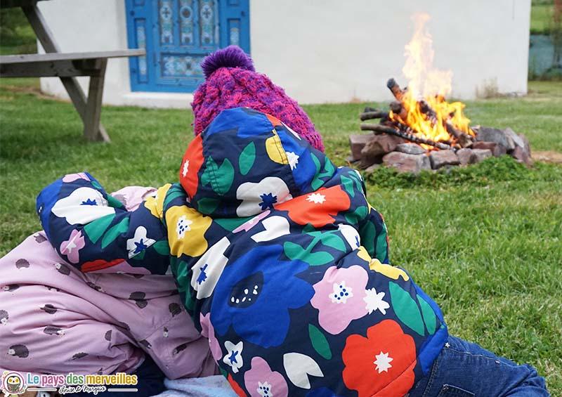enfant devant une yourte et un feu de bois