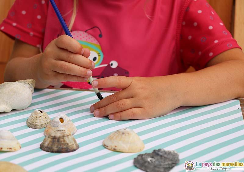 activité enfant de peinture sur des coquillages