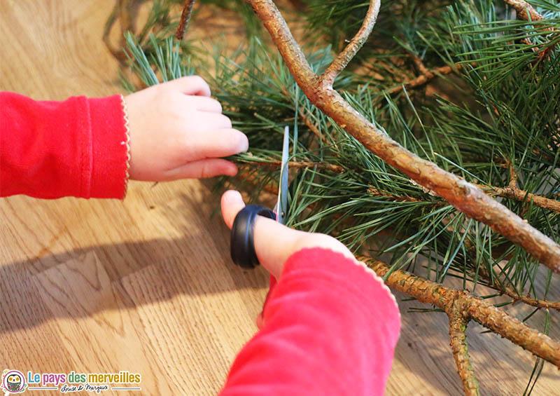 Couper des branches des branches de pin pour faire une couronne de Noël