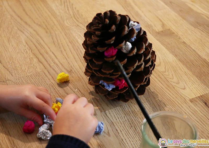 coller des boulettes de papier sur une pomme de pin