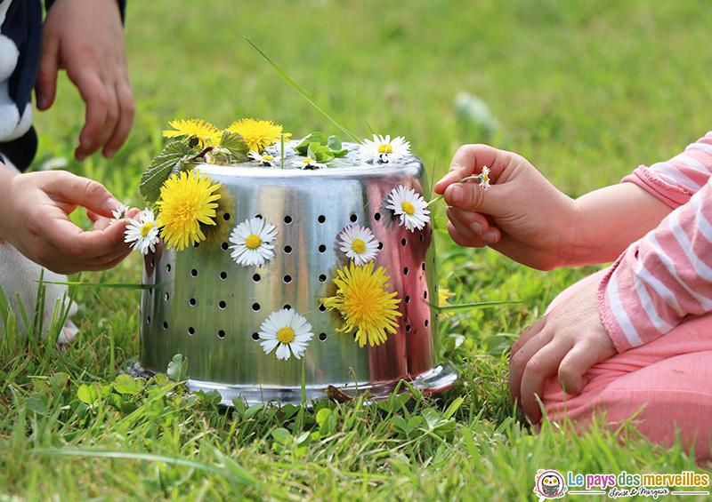 land art avec une passoire et des fleurs