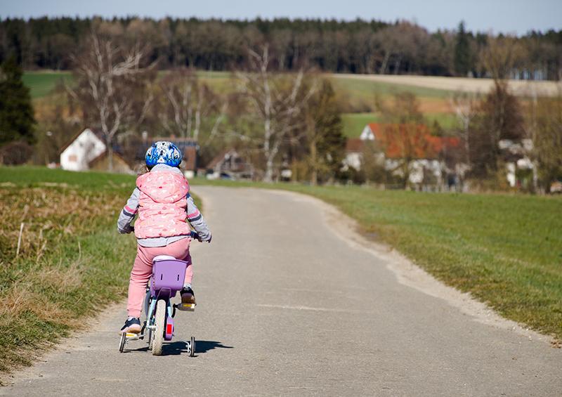 enfant qui fait du vélo avec stabilisateurs