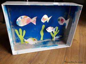 aquarium dans une boite en carton avec des poissons suspendus