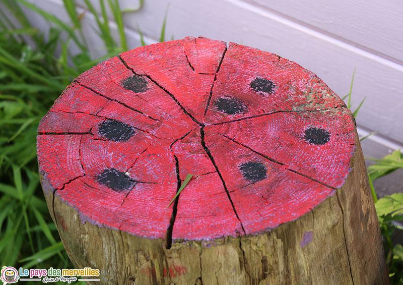 dessin de coccinelle sur un bûche en bois