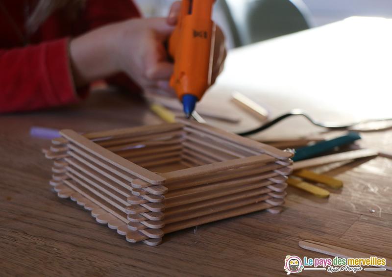 Coller des bâtonnets de bois pour fabriquer une mangeoire