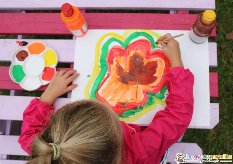 Enfant de maternelle qui peint le contour d'une feuille d'automne