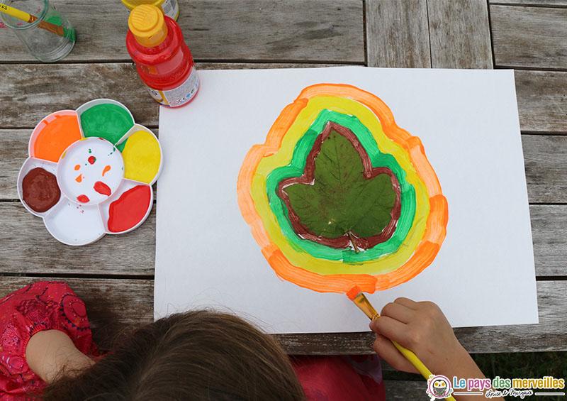 Enfant de primaire qui peint le contour d'une feuille d'arbre
