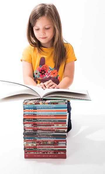 Petite fille qui lit une pile de livres