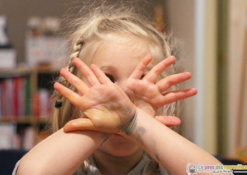 Mains enfant devant le visage après une séance de peinture