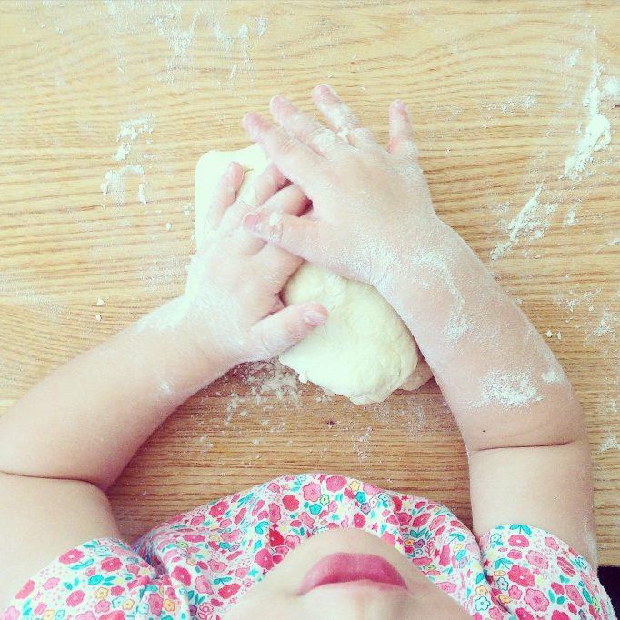 enfant qui pétrit une pâte à pain