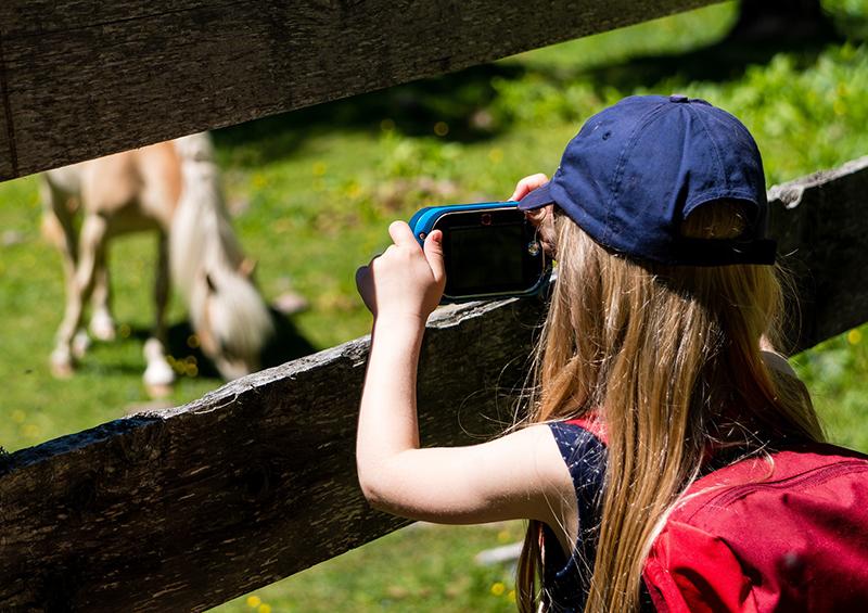 enfant qui prend des photos dans la nature
