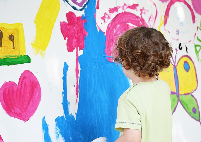 occuper ses enfants avec de la peinture sur un mur recouvert de papier