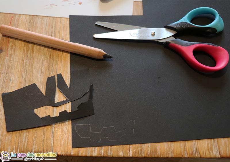 Visage de citrouille découpé dans du papier noir